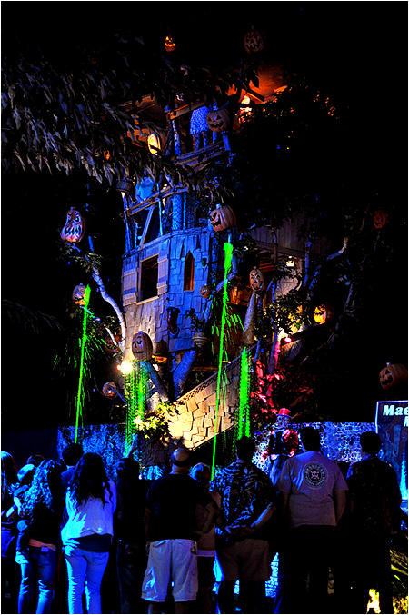 Bubbling cauldrons burst green liquids in front of a giant treehouse with ornate jack-o-lanterns flashing all over it.