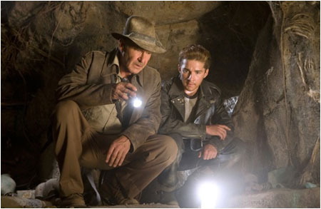 Why is Indy shining a flashlight on another light?